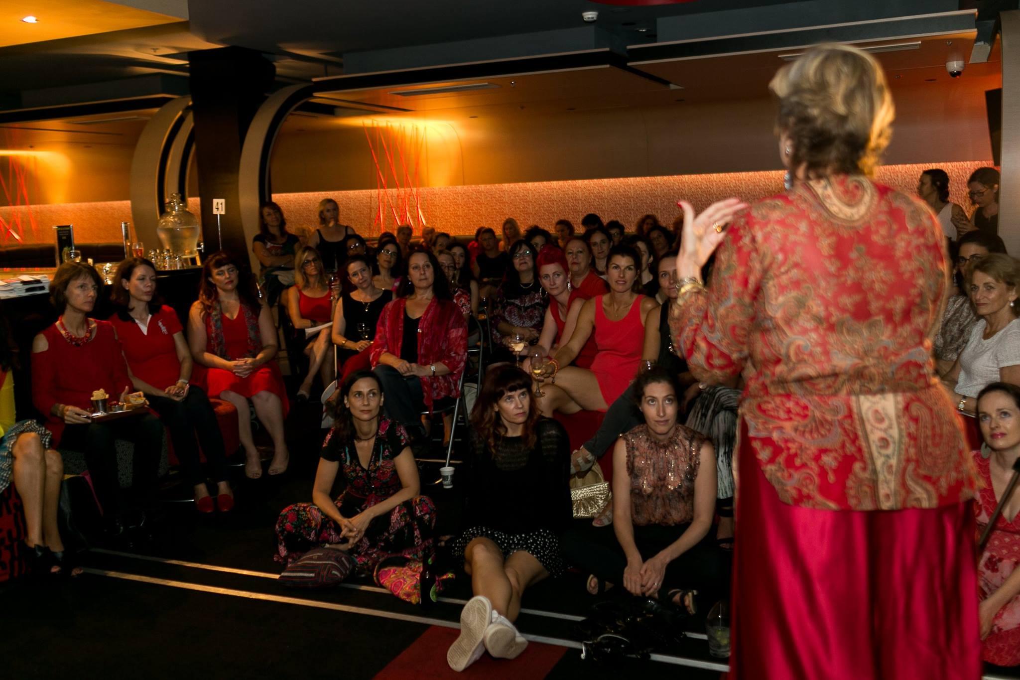 A room full of women in red listening to guest speaker Maree Lipschitz