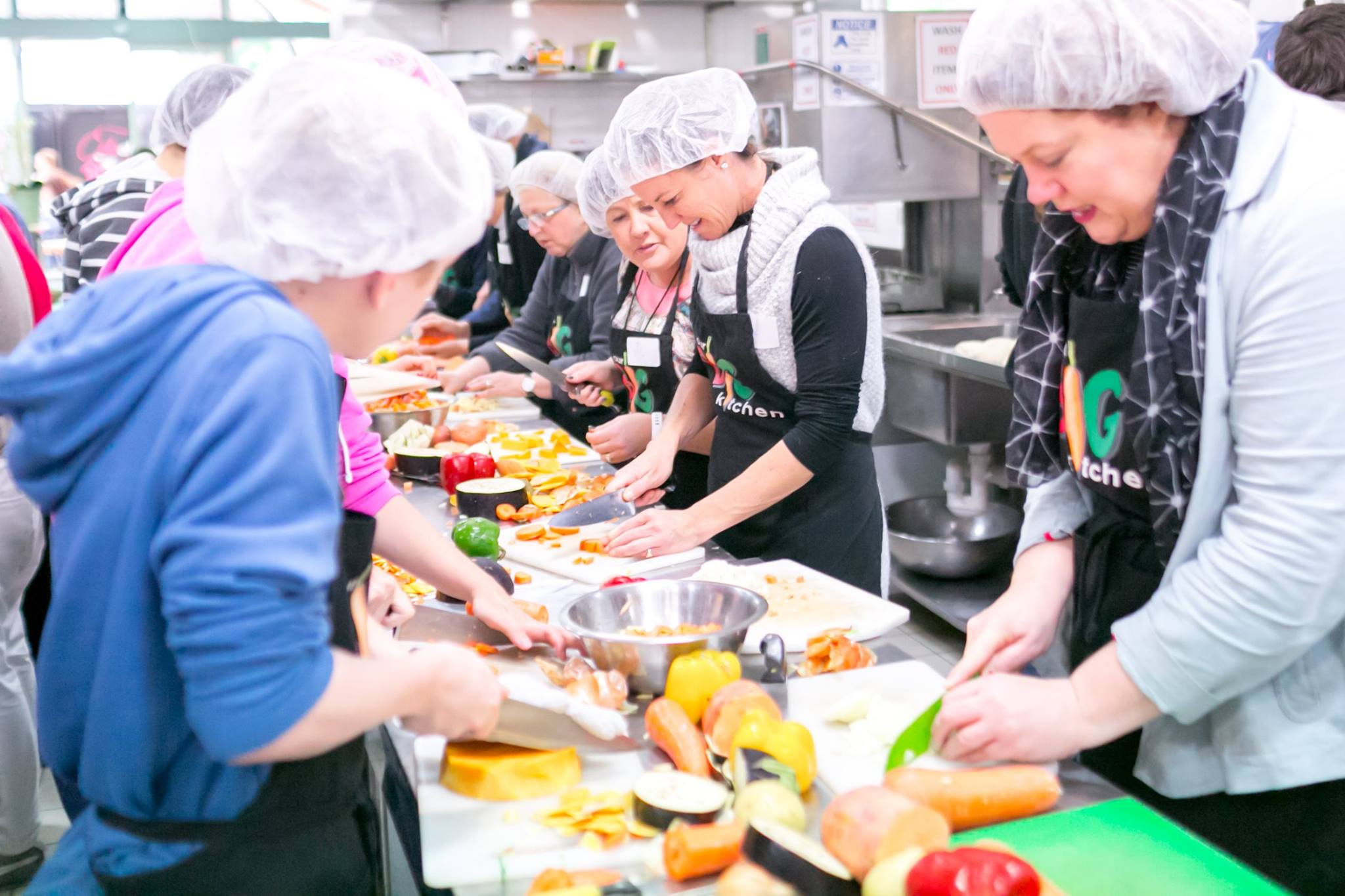 Adults and teens in the kitchen helping to prepare hot meals