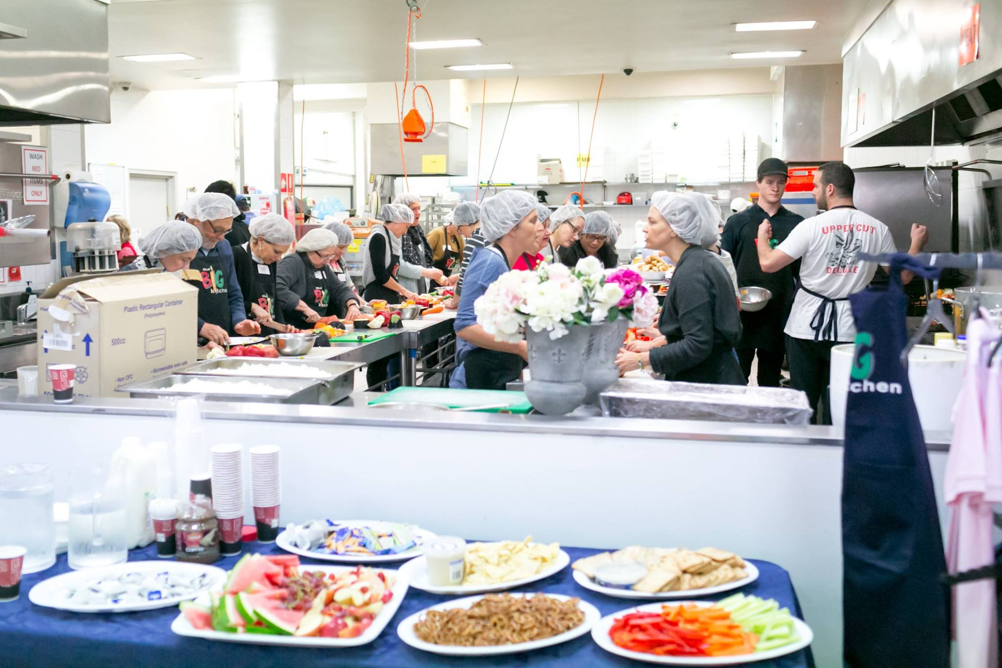 Adults and teens in the kitchen helping to prepare hot meals to be delivered to the homeless and people in need around Sydney