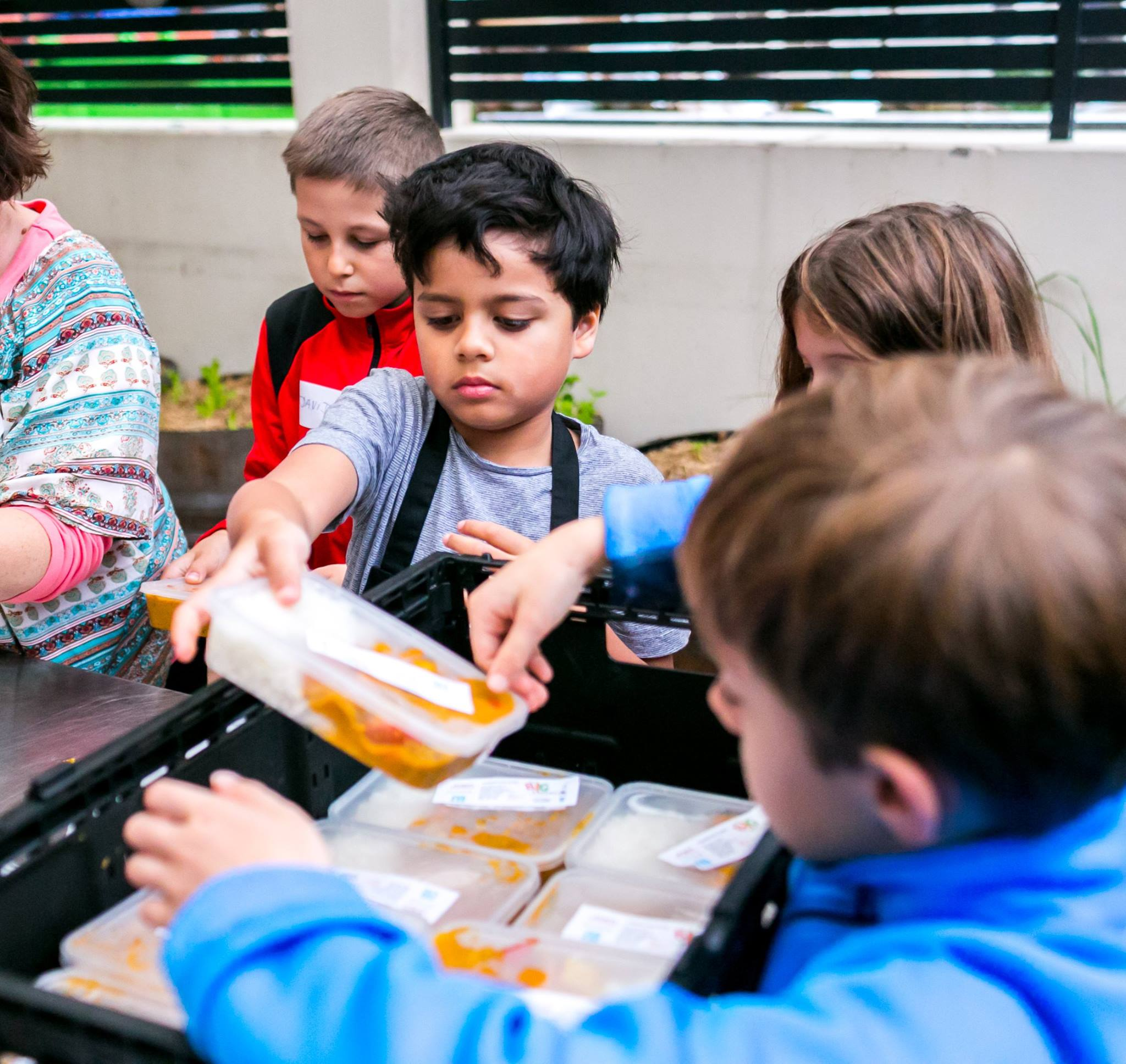 Kids helped to pack the vegetable curry and soup that the volunteers helped prepare earlier in the day
