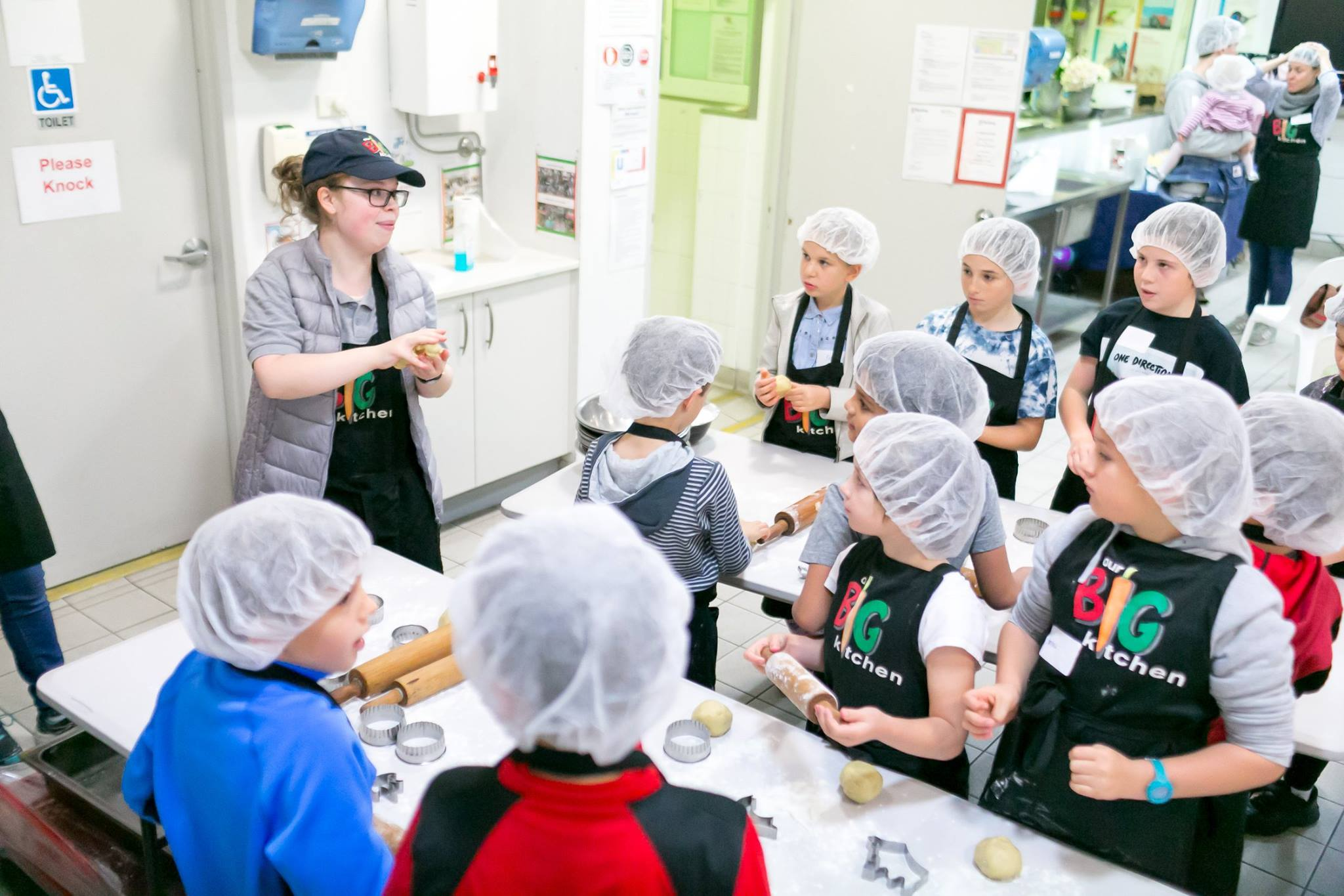 Sandy from Our Big Kitchen teaching all the kids how to make cookies and bread rolls